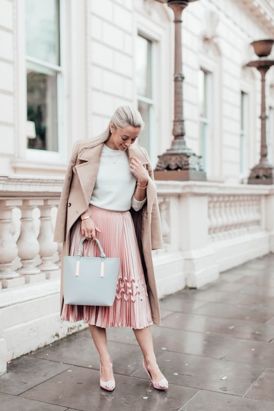 a white sweater, a pink pleated midi, pink floral shoes, a camel coat and a grey tote