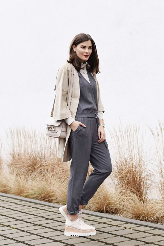 a minimalist outfit with a white turtleneck, a grey jumpsuit, white platform shoes, a grey blazer and a grey bag
