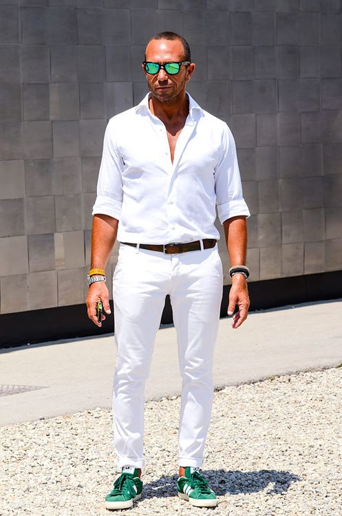 a summer look with a white shirt, white jeans, bright green sneakers and matching sunglasses