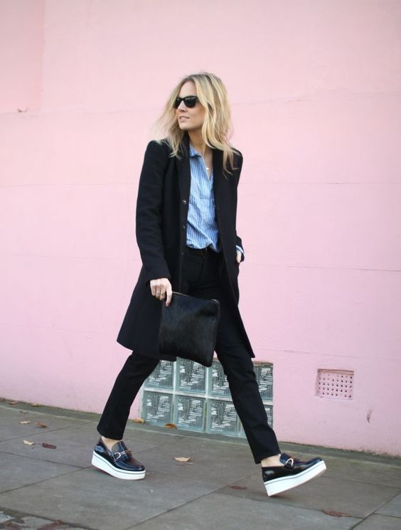 a black pantsuit with a long blazer, a blue striped shirt, black platform loafers and a black clutch