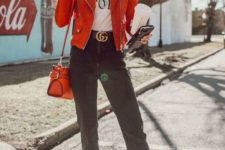 06 a red suede jacket, a white graphic t-shirt, black washed crop jeans, a black logo belt, white booties, round aviator sunglasses and a red shoulder bag