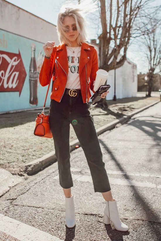 a red suede jacket, a white graphic t-shirt, black washed crop jeans, a black logo belt, white booties, round aviator sunglasses and a red shoulder bag