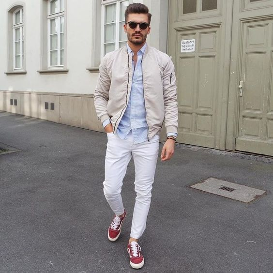 a spring look with a light blue shirt, a tan bomber jacket, white jeans and red sneakers is veyr comfy