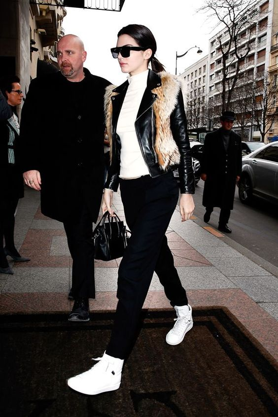 a white turtleneck, black pants, white high tops, a black leather jacket and a black bag