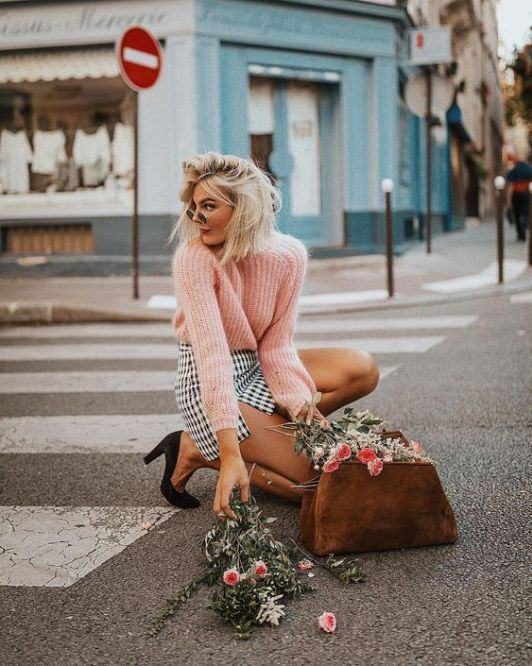 a pink oversized sweater, a printed monochromatic mini skirt, black shoes and a brown bag