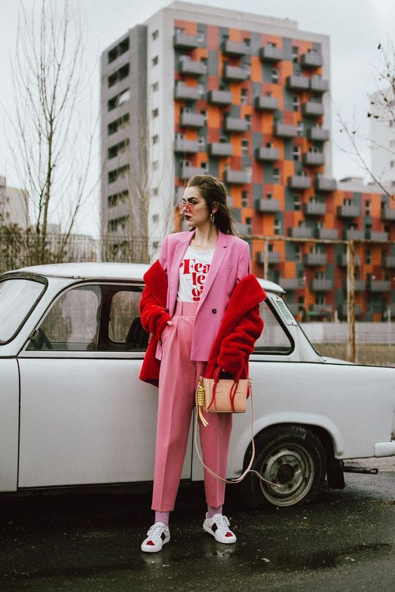 a pink pantsuit with cropped pants, a printed tee, a red faux fur jacket and bright sneakers
