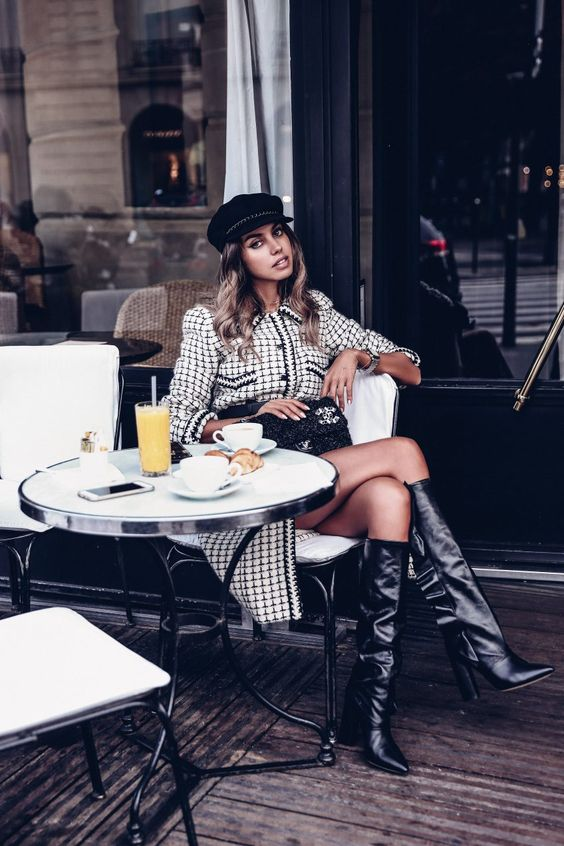 a printed monochromatic dress, black boots, a black bag and a cap for a Paris chic look