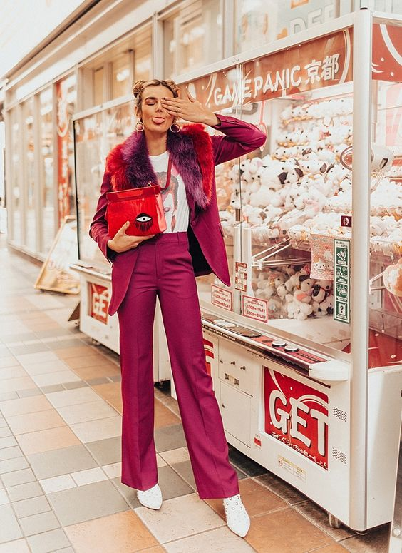 a fuchsia pantsuit with some colorful faux fur, white shoes, a printed tee and a whimsical red bag