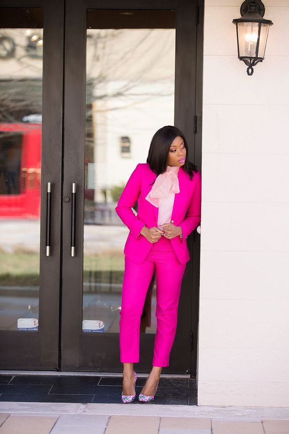 a hot pink pantsuit, a blush blouse with a large bow and bright floral shoes for a work day