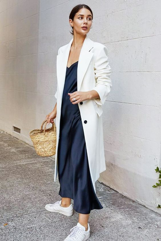a minimalist look with a black silk slip midi dress, a white trench, white sneakers and a basket