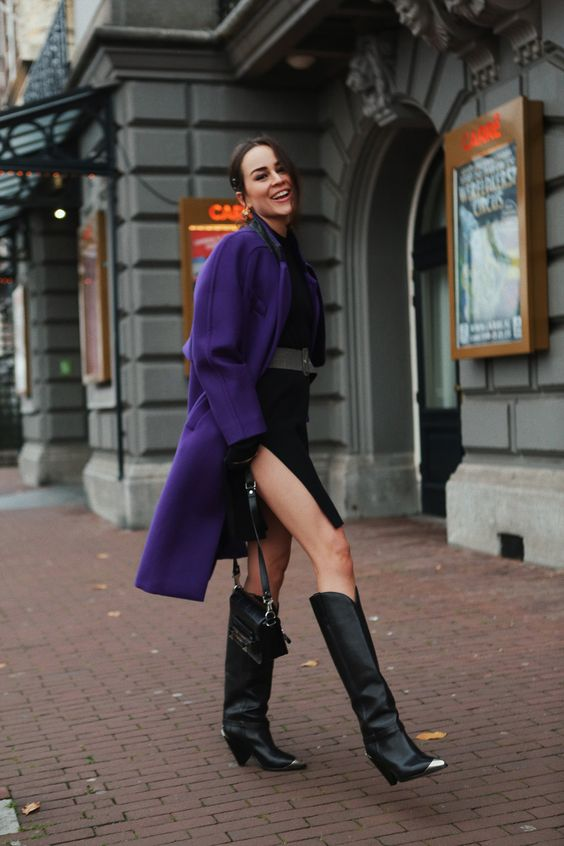 black knee boots, a black dress with a side slit, a purple coat and a black bag for a contrasting look