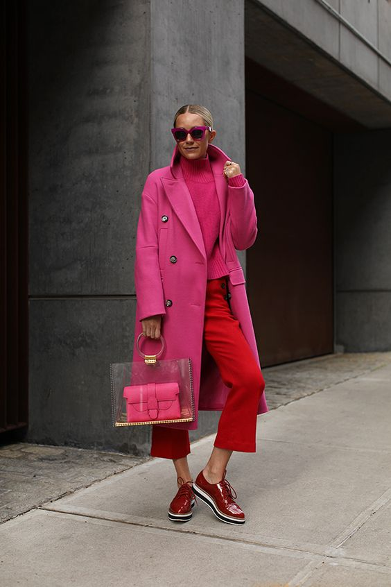 a pink turtleneck sweater, red cropped pants, red shiny shoes, a pink coat and a creative bag