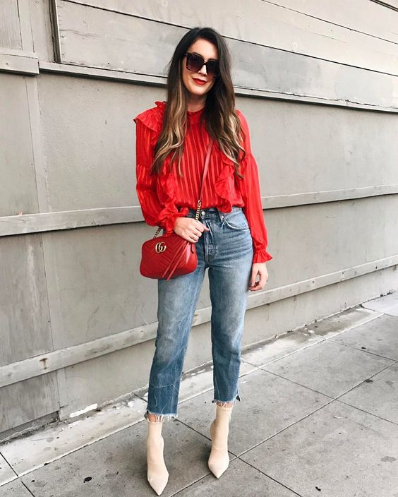 a red striped blouse with ruffles, blue straight cropped jeans, white sock booties and a red bag