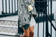 11 an oversized printed sweatershirt, a white mini, brown knee boots, a small white bag