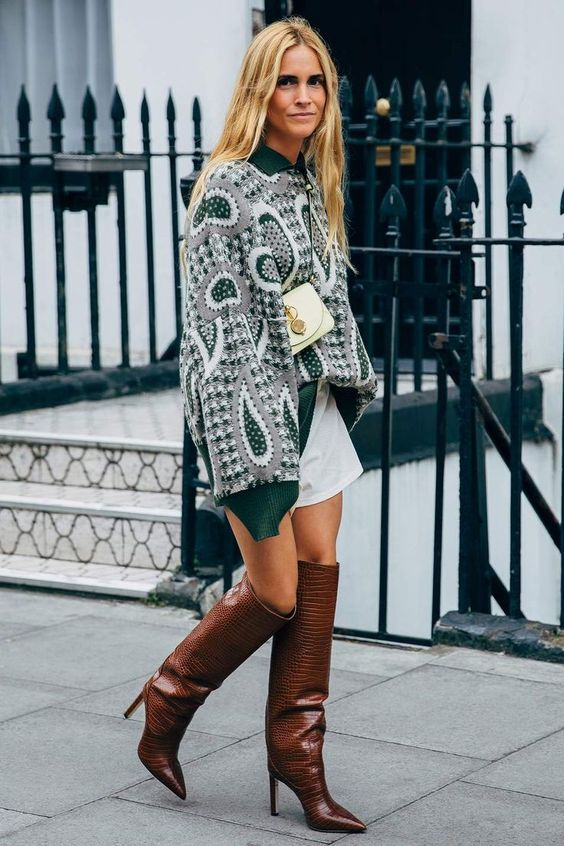 an oversized printed sweatershirt, a white mini, brown knee boots, a small white bag