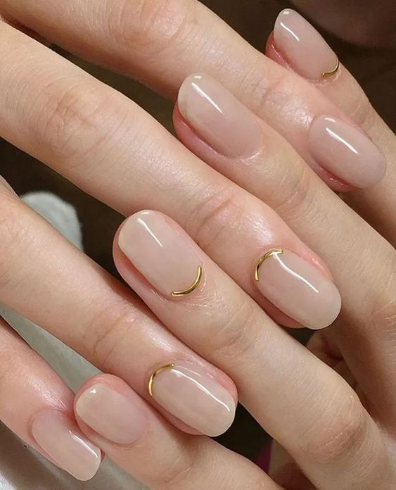 a contrarious micro French manicure done in blush and with gold curves is a chic and bold idea