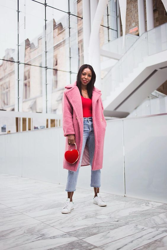 a red top, blue straight jeans, white sneakers, a pink faux fur coat and a red heart-shaped bag