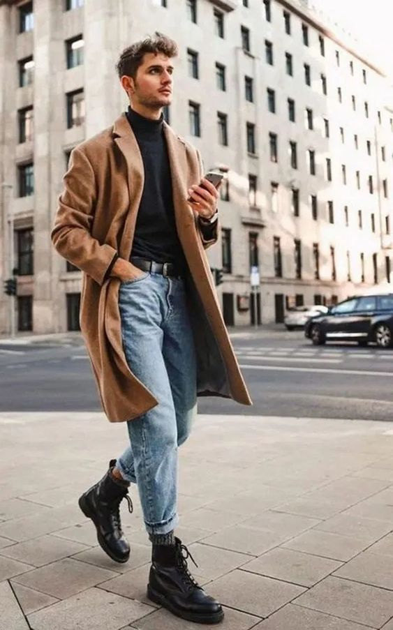 a winter look with a black turtleneck, light blue jeans, black boots and a classic camel coat