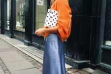 13 a bright winter look with an orange oversized sweater, a blue silk midi, colrful trainers and a polak dot clutch