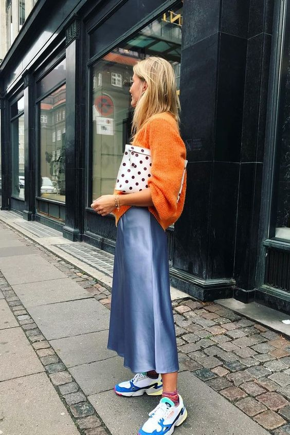 a bright winter look with an orange oversized sweater, a blue silk midi, colrful trainers and a polak dot clutch