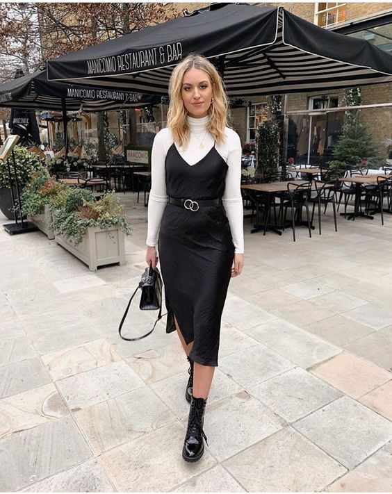 a white turtleneck, a black silk slip midi dress, black combat boots and a black bag