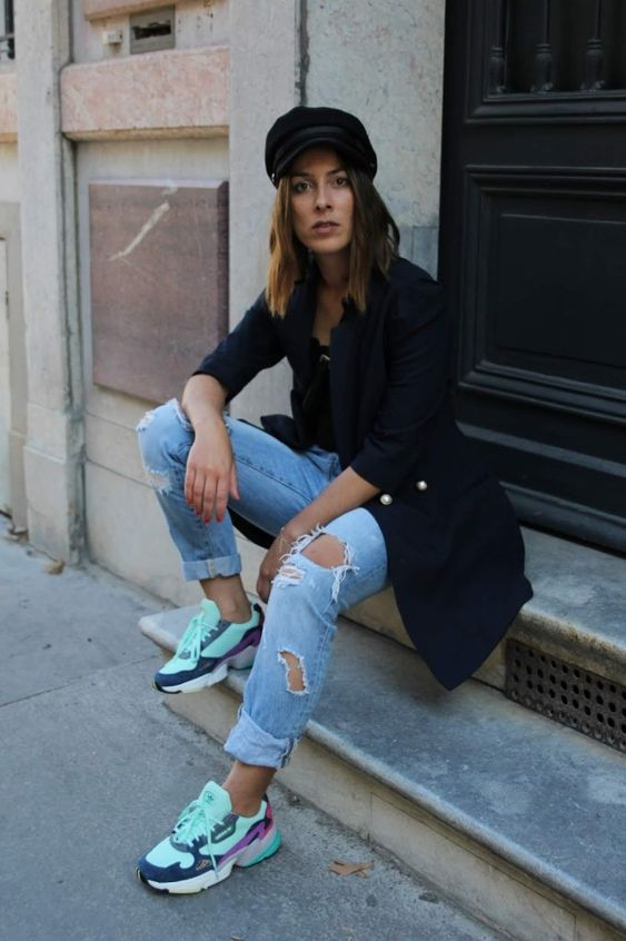 a spring outfit with a black long blazer, a black top, blue ripped jeans, colorful trainers and a cap