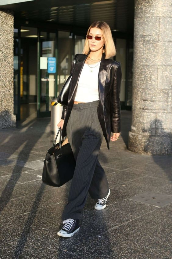 Bella Hadid wearing a white crop top, grey striped pants, black sneakers and a black leather blazer