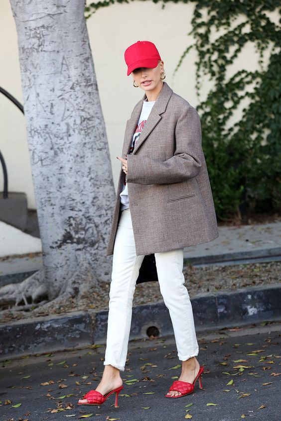 Hailey Baldwin wearing a printed tee, white jeans, an oversized tweed blazer, a pink cap and matching square toe shoes
