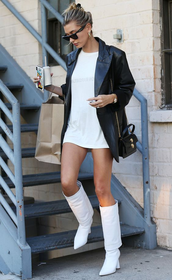 Hailey Baldwin wearing a white sweatshirt, white boots, a black leather blazer and a black bag
