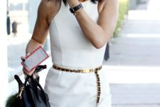 Kylie Jenner wearing a minimalist white fitting mini dress with no sleeves, a black chain belt and carrying a black bag