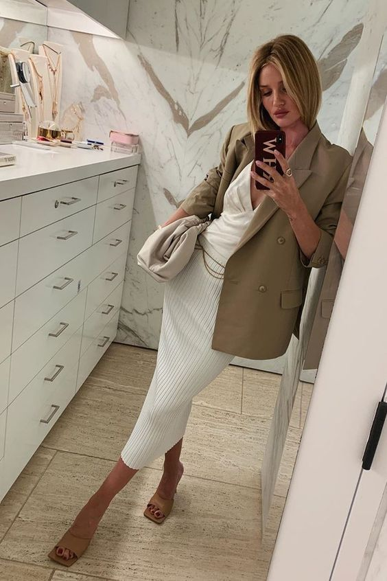 Rosie Huntington whiteley wearing a white top, a striped midi pencil skirt, nude suqare toe heels and an olive green blazer