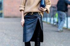 With beige loose sweater, clutch and black lace up over the knee boots