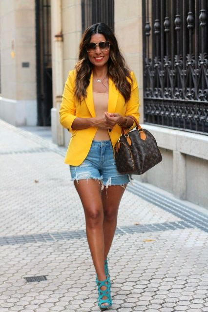 With beige top, yellow blazer, printed bag and sandals