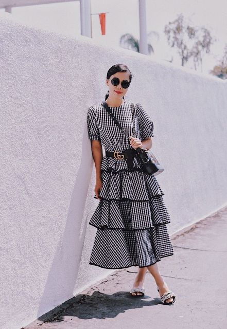 With black crossbody bag, rounded sunglasses and mules