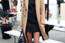 With black mini dress, beige knee-length coat, black bag and sunglasses
