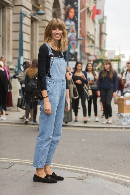 With black shirt, denim jumpsuit and mini bag