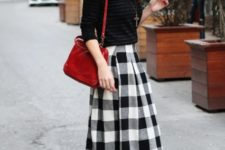 With black shirt, red bag and plaid midi skirt