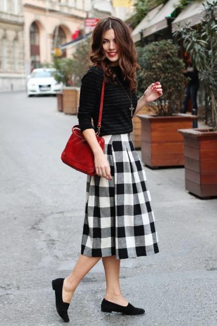 With black shirt, red bag and plaid midi skirt