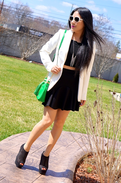 With black top, white blazer, cutout shoes and green bag