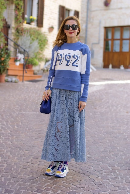 With blue and white labeled sweatshirt, blue bag and colorful sneakers