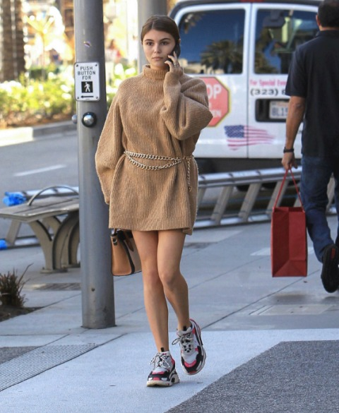 A sweater dress with chain belt, brown leather bag and colorful sneakers