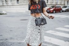 With labeled shirt, black leather crossbody bag and black sneakers