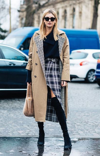 With navy blue shirt, beige trench coat, fur bag and black over the knee boots
