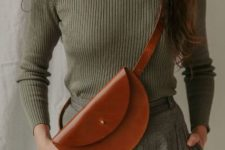 With olive green turtleneck and gray tweed trousers