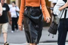 With orange sweater and ankle strap high heels