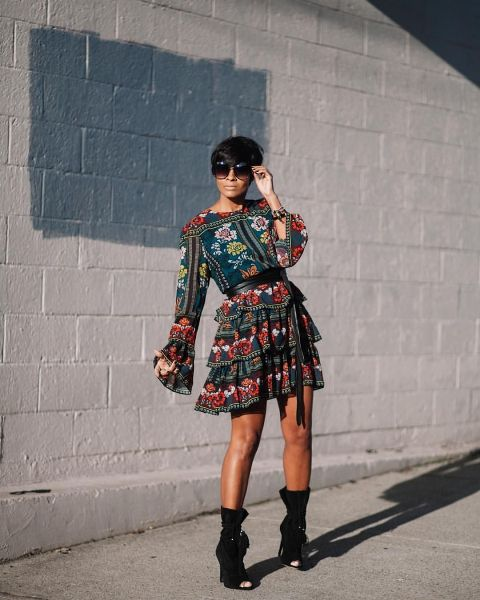 With oversized sunglasses and black cutout mid calf boots
