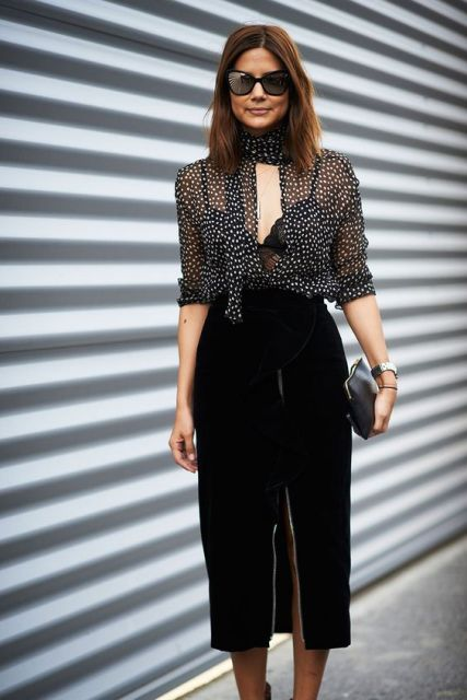 With polka dot blouse and black leather clutch