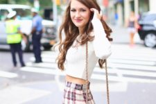 With white cropped shirt and brown leather chain strap bag