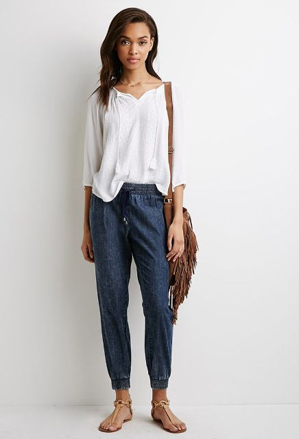 With white loose shirt, brown fringe bag and flat sandals