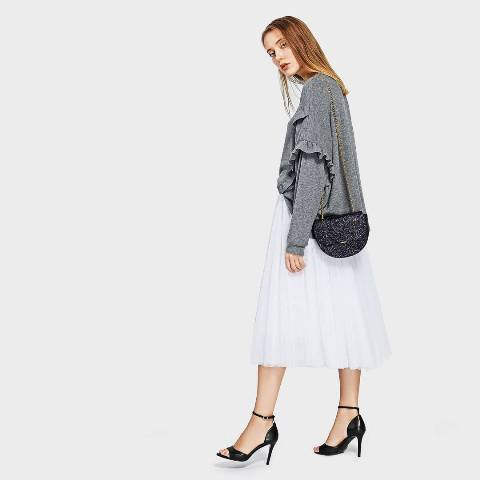 With white pleated midi skirt, black ankle strap shoes and gray loose sweater